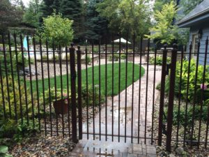 Dark brown ornamental iron gate with arch and quad flare finials